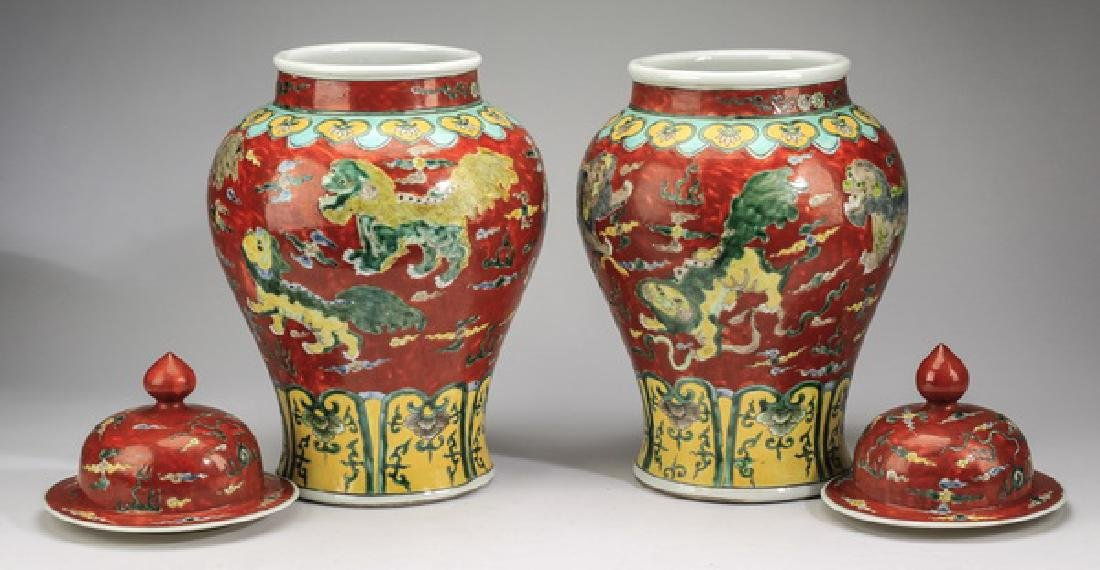 "(2) Chinese red ground, Fu lion jars, 20""h - 6"