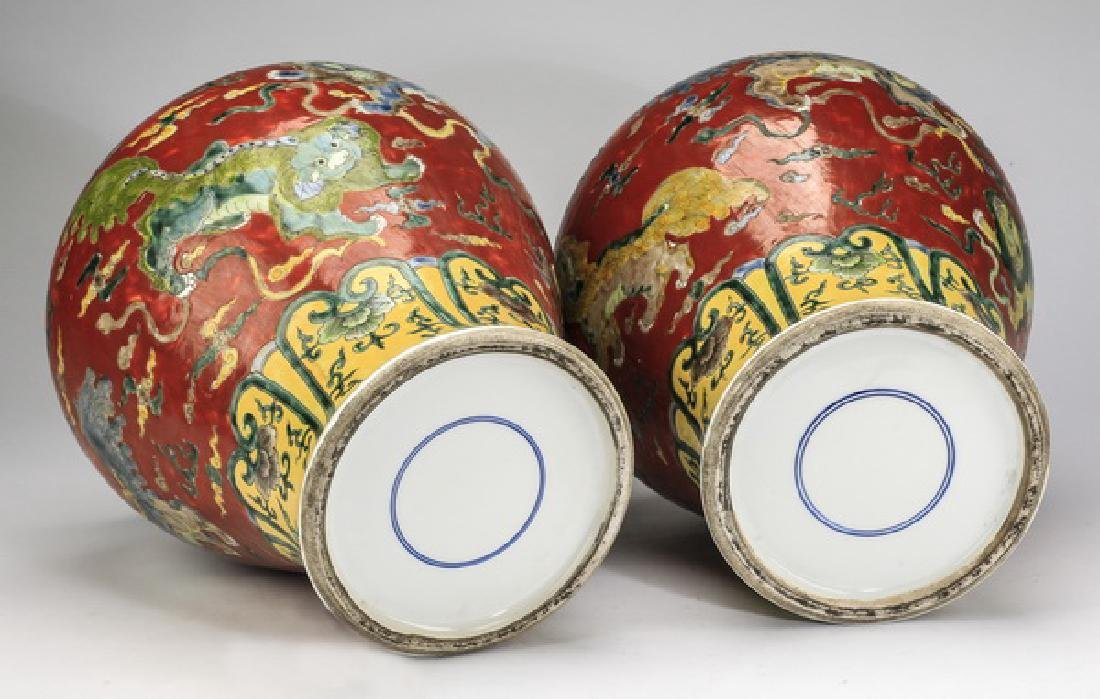 "(2) Chinese red ground, Fu lion jars, 20""h - 8"