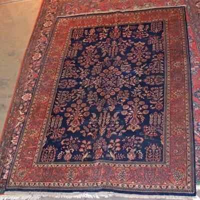 13: Handmade blue floral & red trim rug