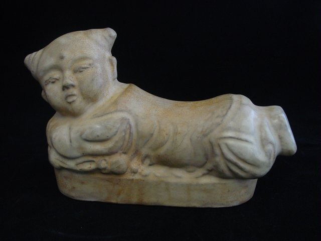 "1222: Porcelain figural pillow depicting ""Child"""