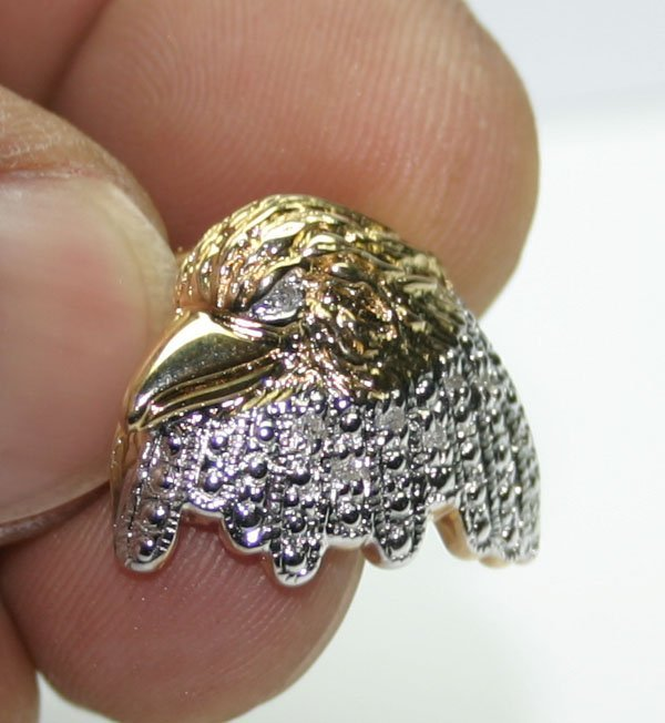 2015: 0.10 CT DIAMOND EAGLE HEAD 10KT GOLD PENDANT.