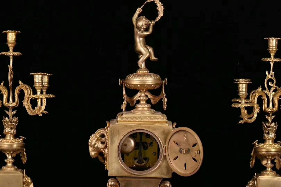A GILT COPPER CLOCK WITH TWO CANDLESTICK - 8