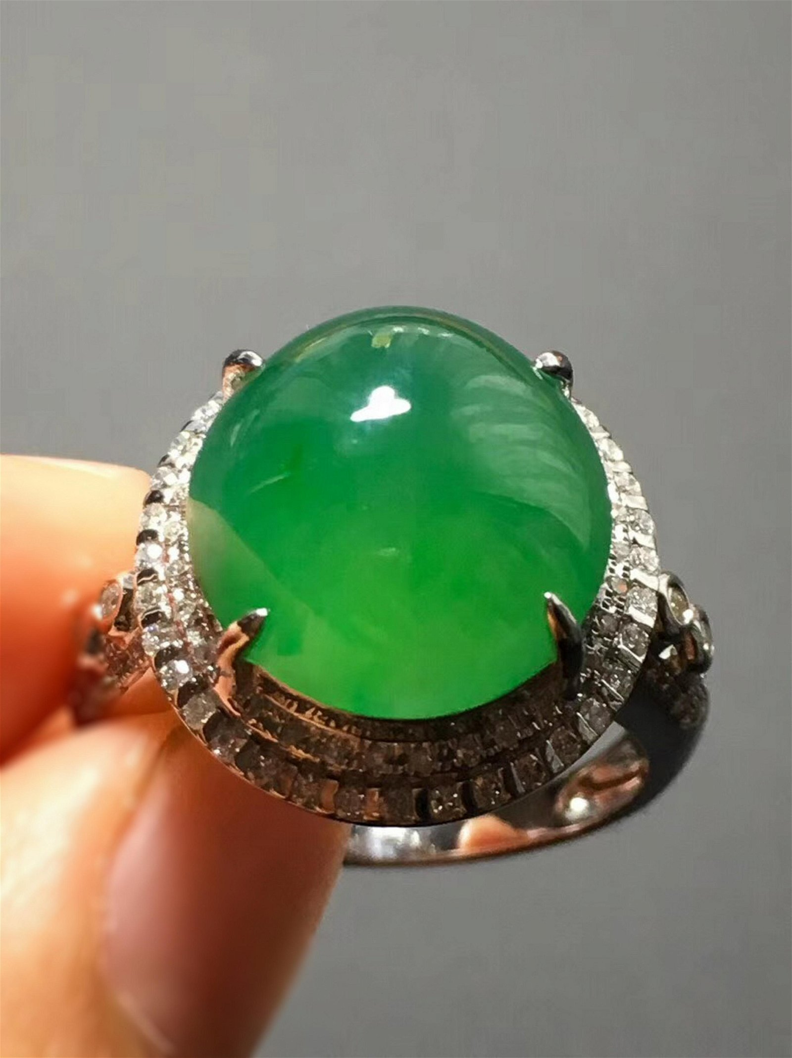 A GREEN JADEITE CARVED CIRCLE RING