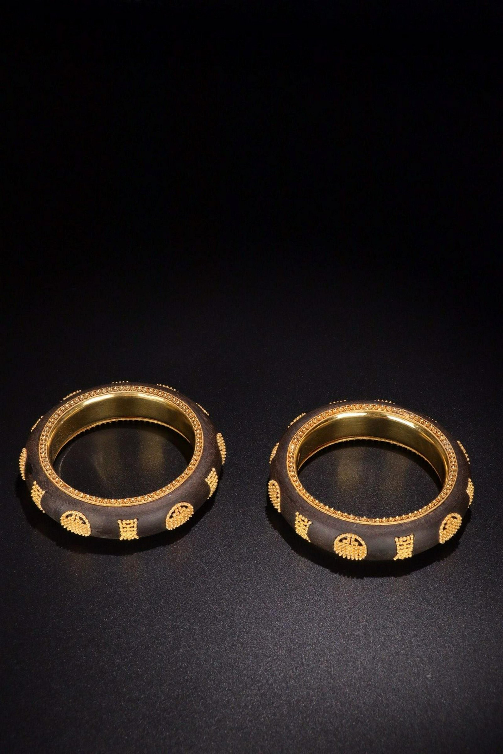 A PAIR OF CHENXIANG WOOD EMBEDED GOLD BANGLES