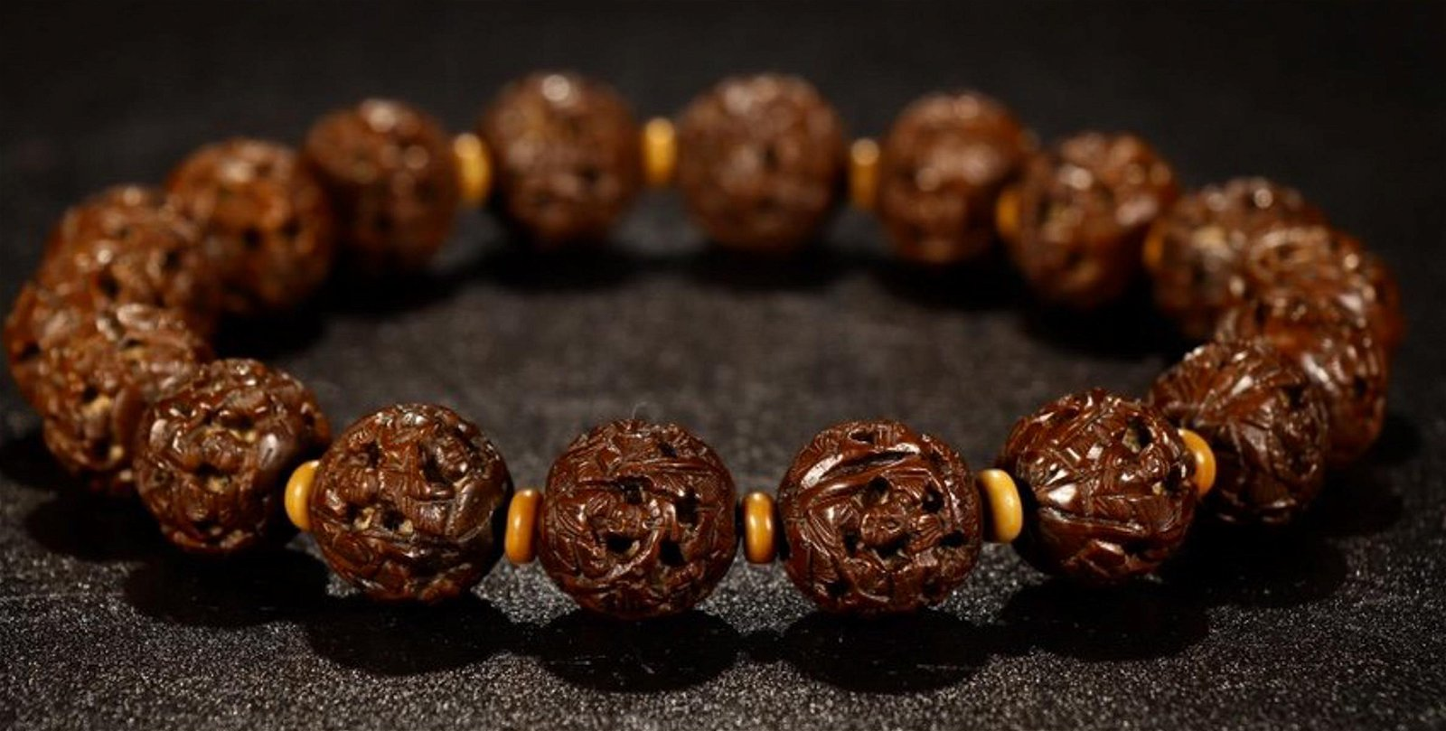 A WALNUT CARVED PINE AND CHARACTER BRACELET