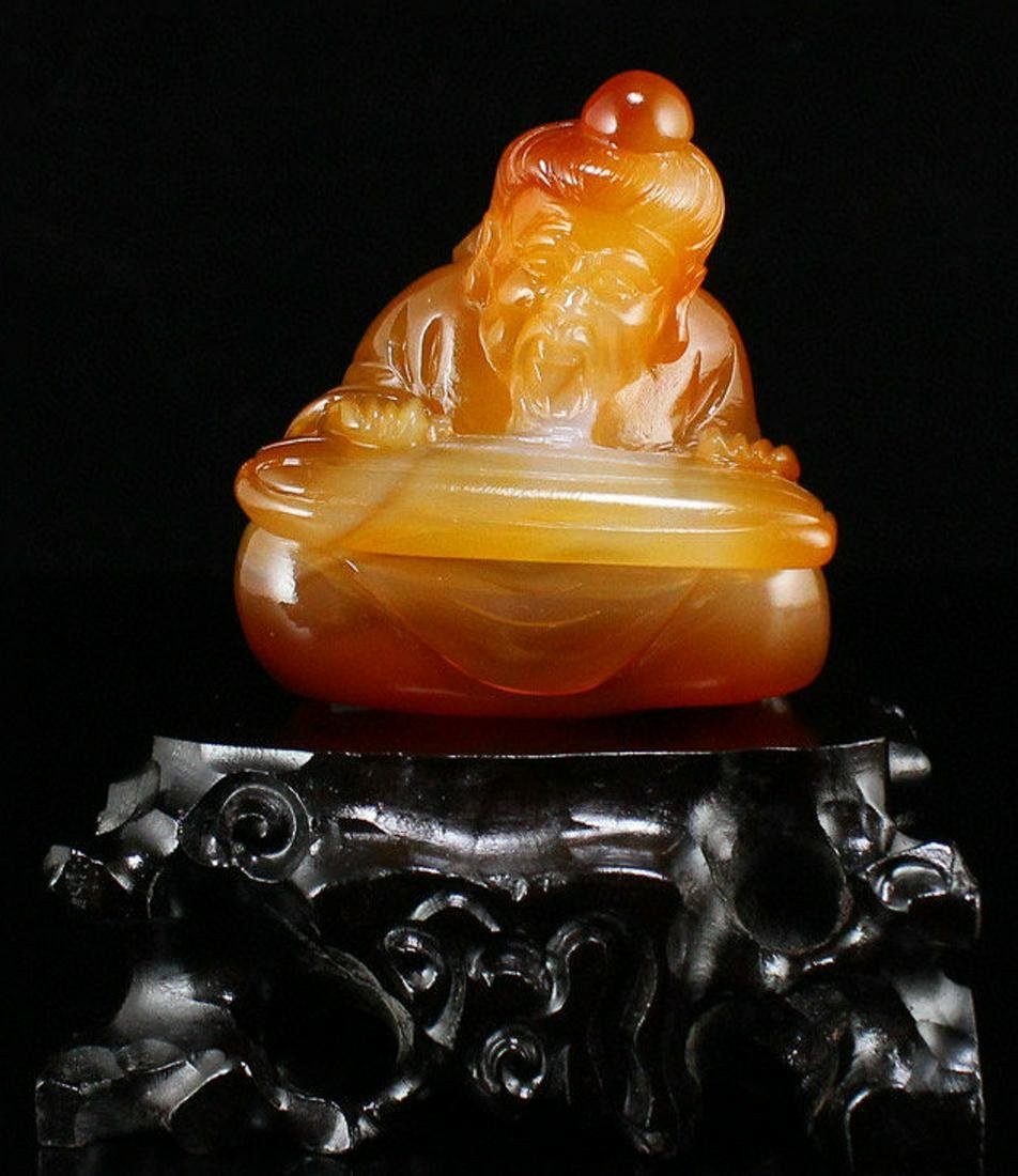 AN AGATE CARVED FIGURE SHAPED PENDANT