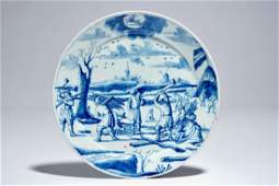 A Dutch Delft blue and white plate with lumberjacks