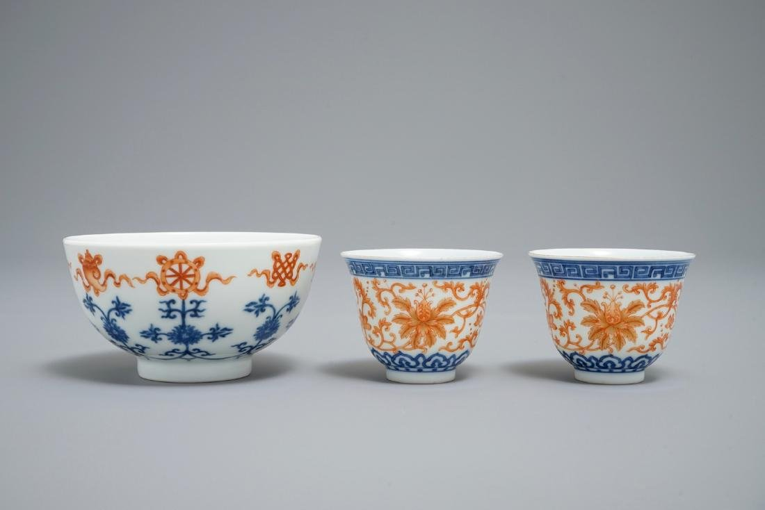 A pair of Chinese iron red and blue cups and a bowl,