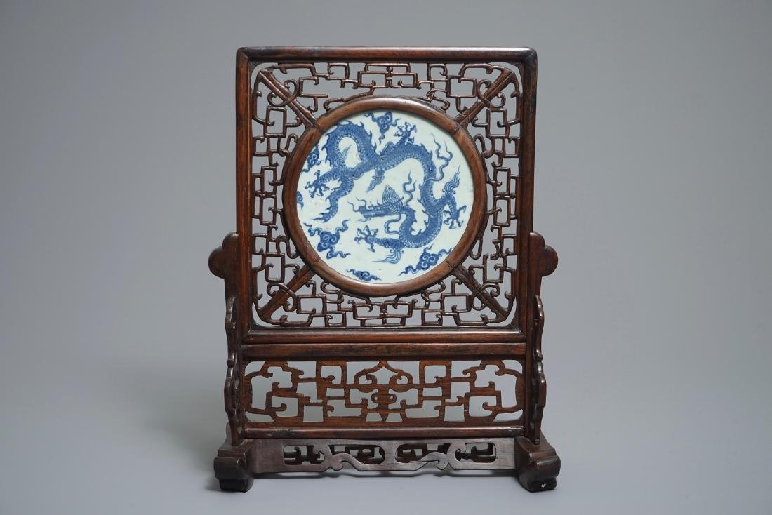 A Chinese carved wood table screen with a blue and