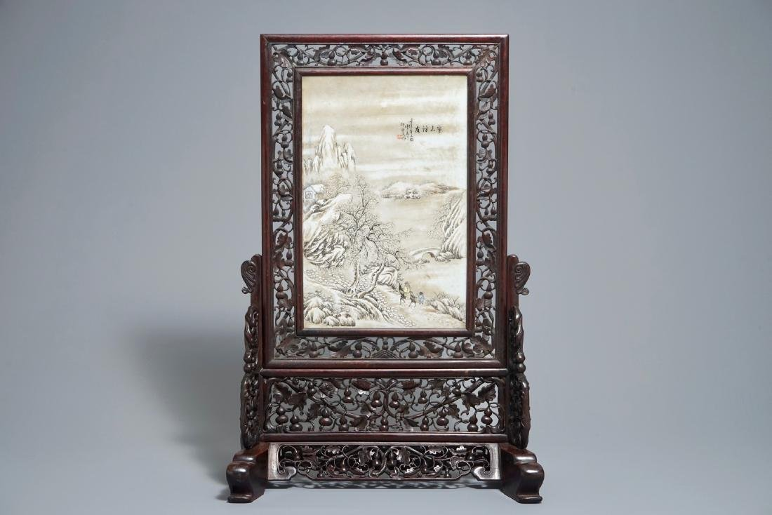 A Chinese carved wood table screen with a porcelain