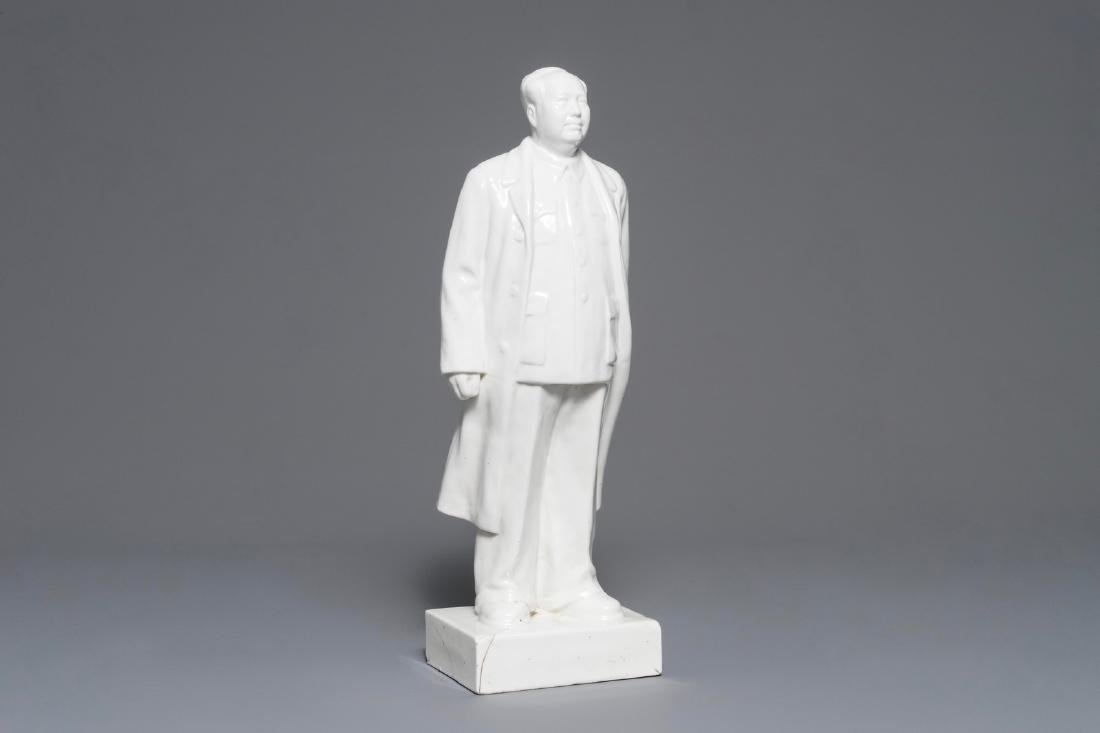 A tall Chinese figure of Mao Zedong standing on a base,