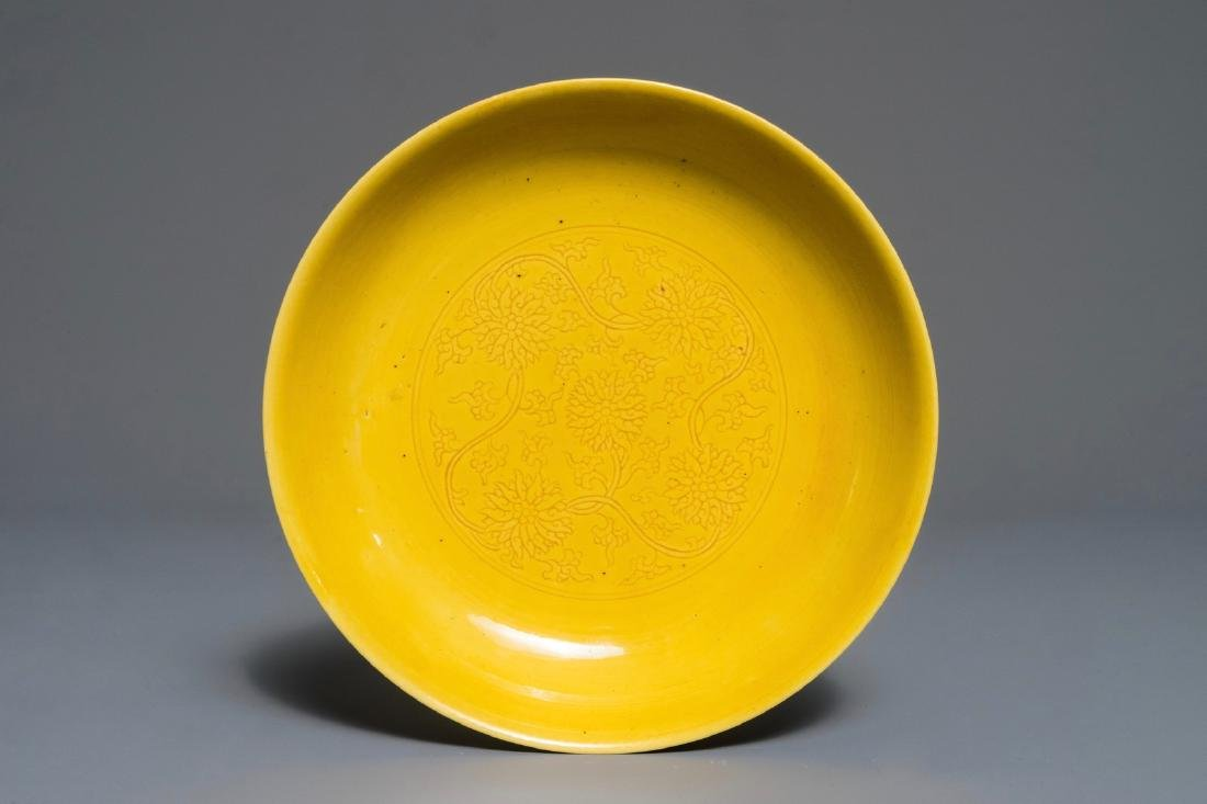A Chinese monochrome yellow dish with incised lotus
