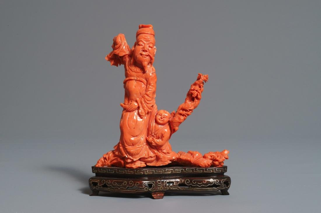 A Chinese carved red coral figure of a sage with a