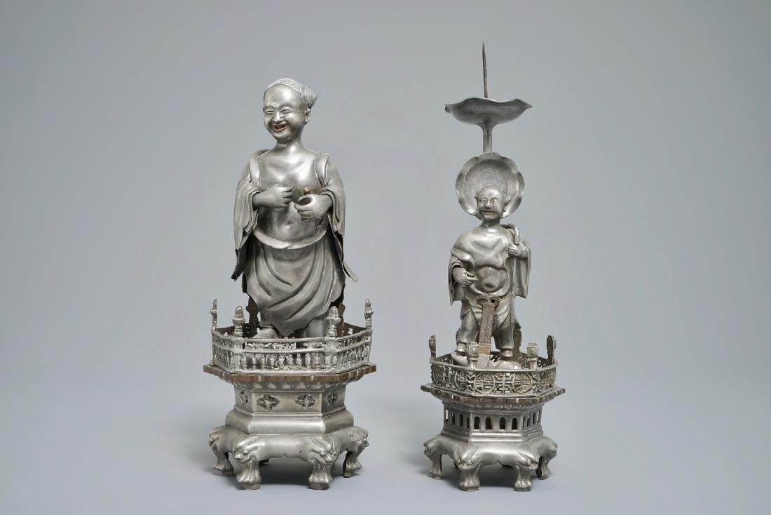 A Chinese pewter candlestick and a figure of a boy,