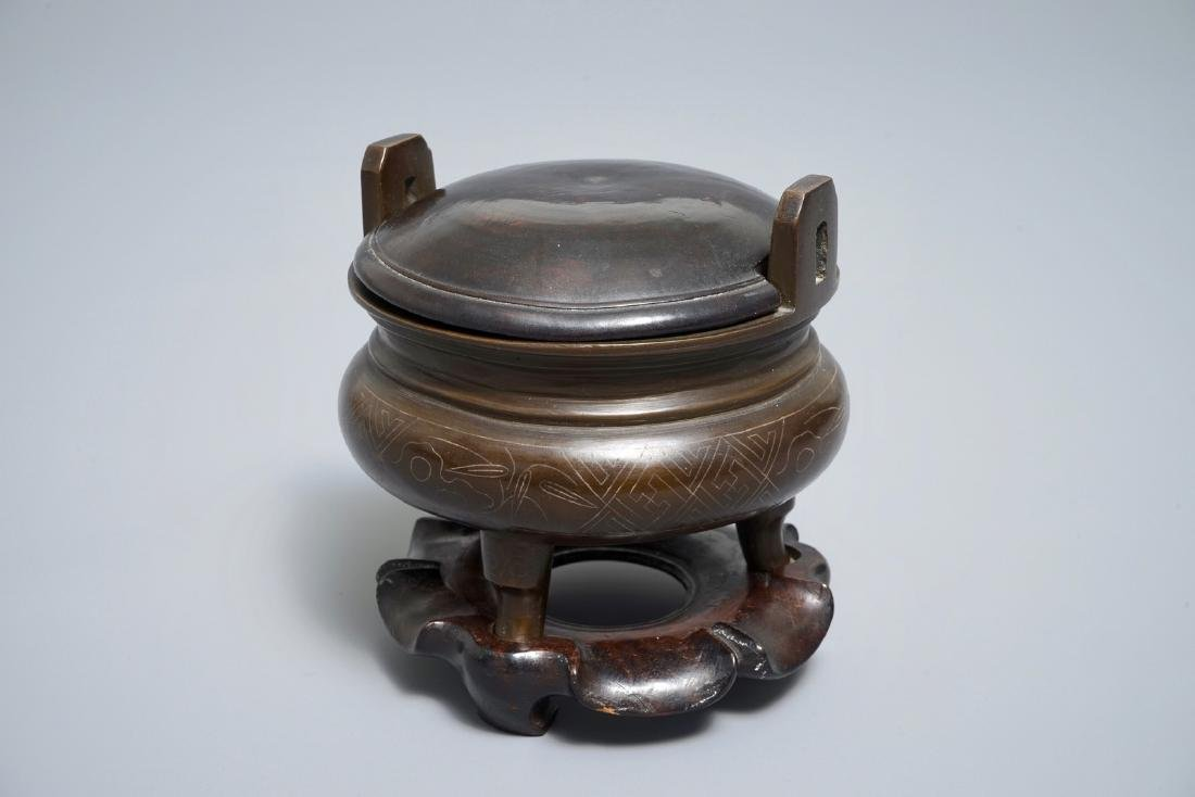 A Chinese silver-inlaid bronze incense burner on stand,