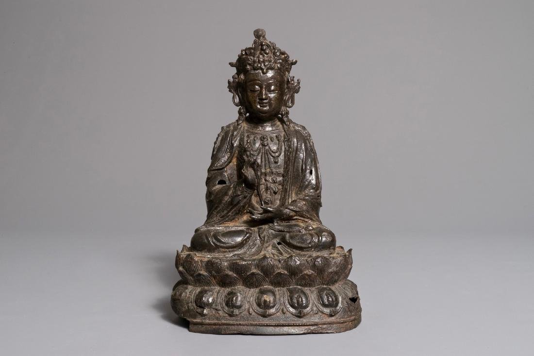 A Chinese bronze figure of Guanyin seated on a lotus