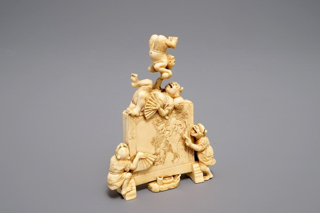 A Japanese carved   okimono with oni around a screen,