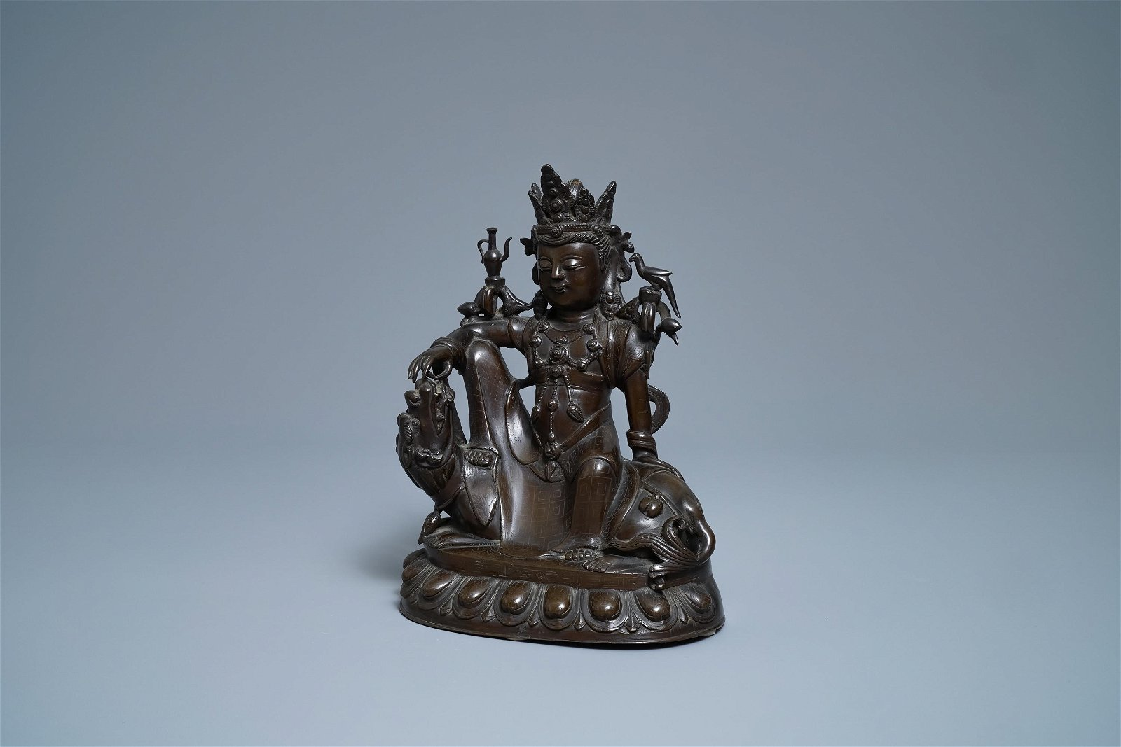 A Chinese silver-inlaid bronze figure of Guanyin on a