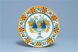 A polychrome Dutch maiolica dish with a fruit tazza,
