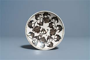 A Chinese Cizhou plate with carved floral design,