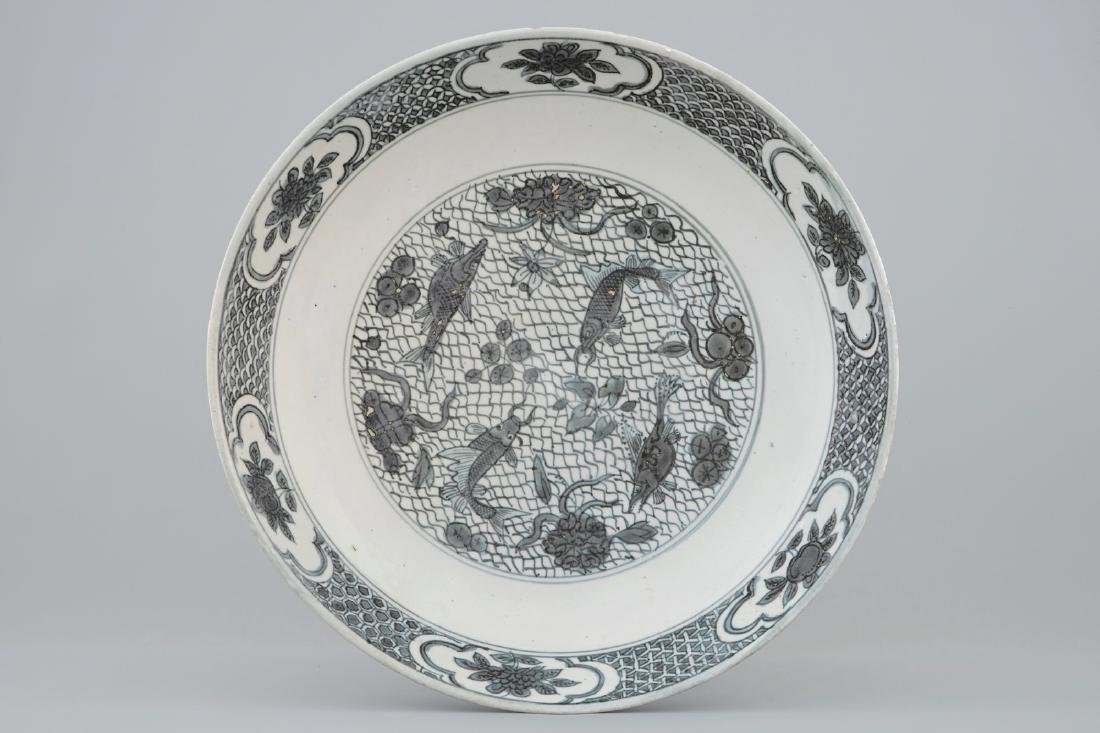 A Chinese Swatow dish with a blue-grey design of fish,