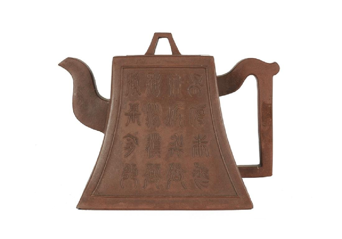 A Yixing teapot, trapezium model with archa•c writing.