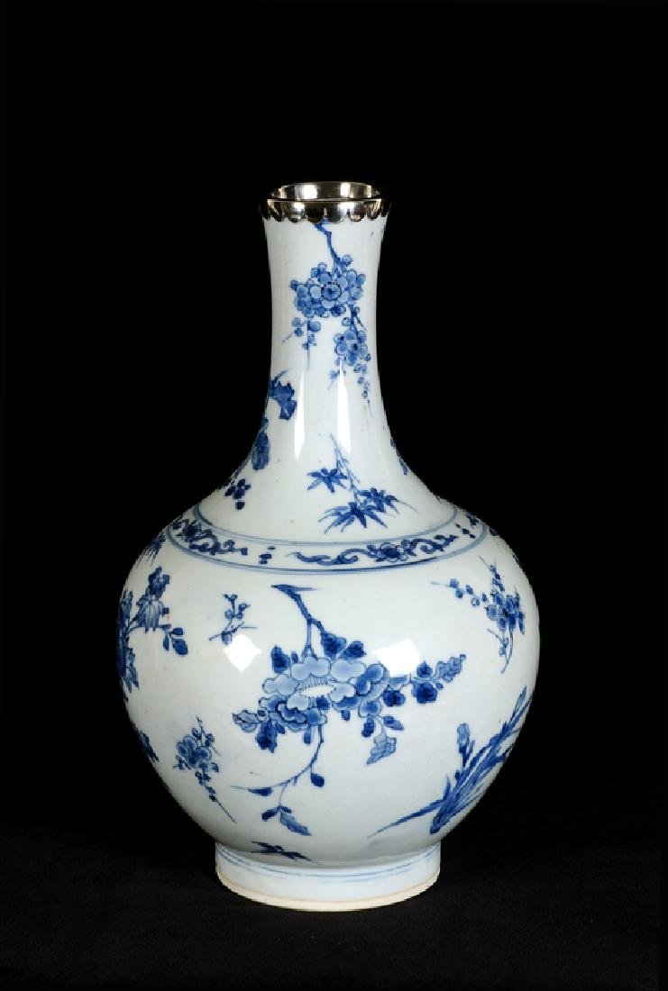 A blue and white porcelain bottle neck vase with silver