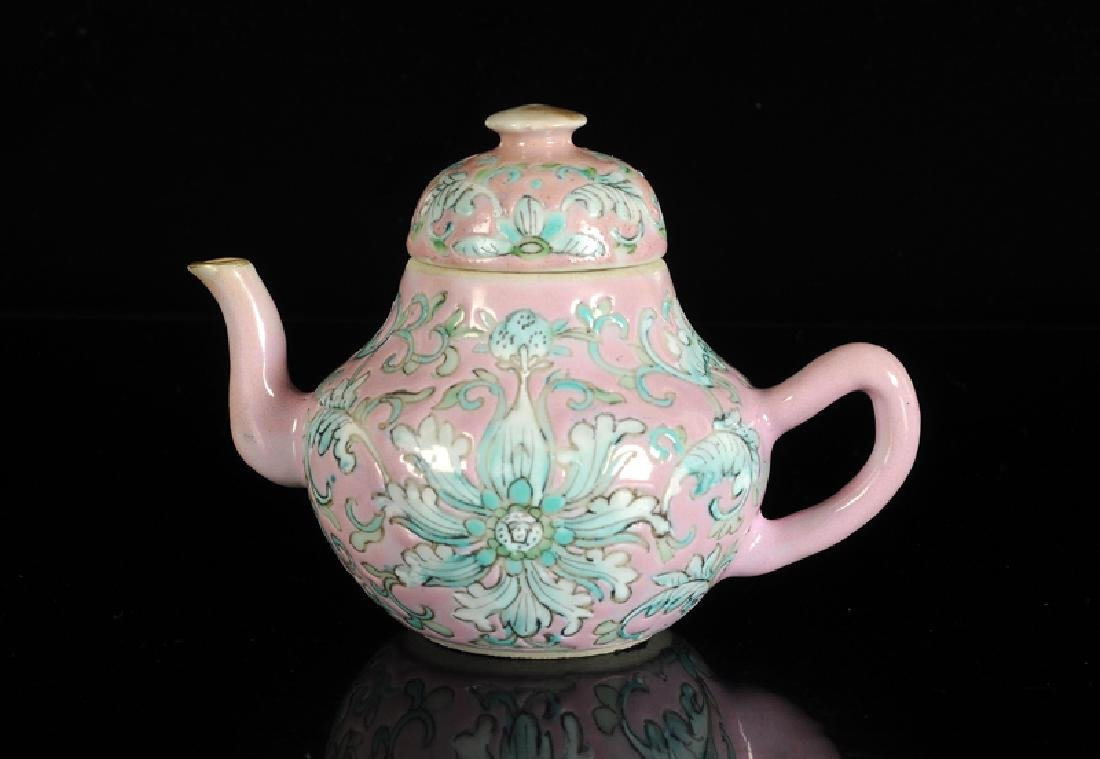 A polychrome teapot with pink fond, decorated with
