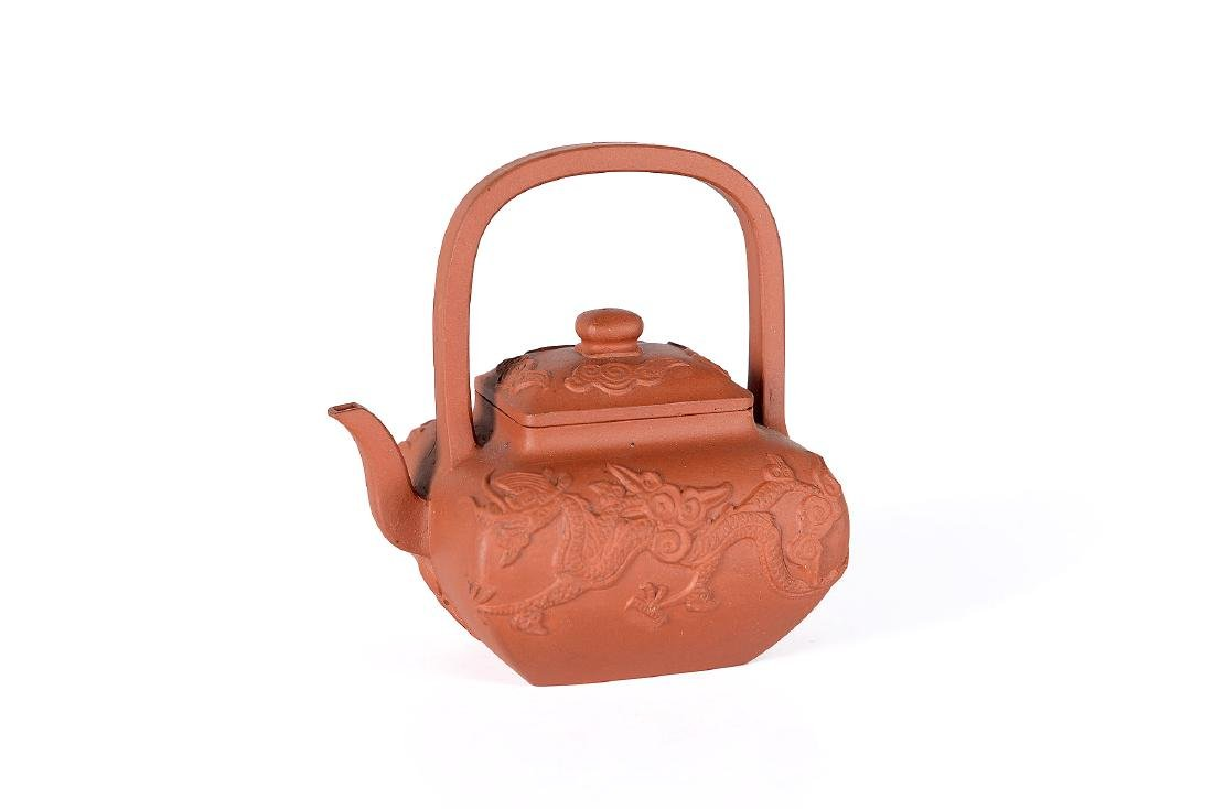 A square-shaped Yixing teapot decorated with dragons.