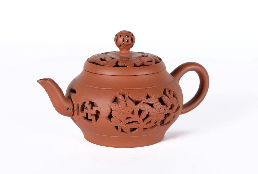 A Yixing teapot with devil's work floral decorations.