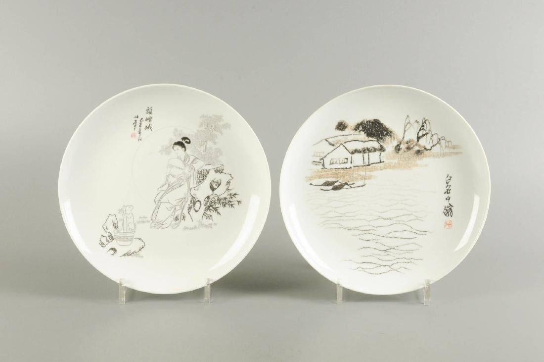 A lot of two black and white porcelain plates, one