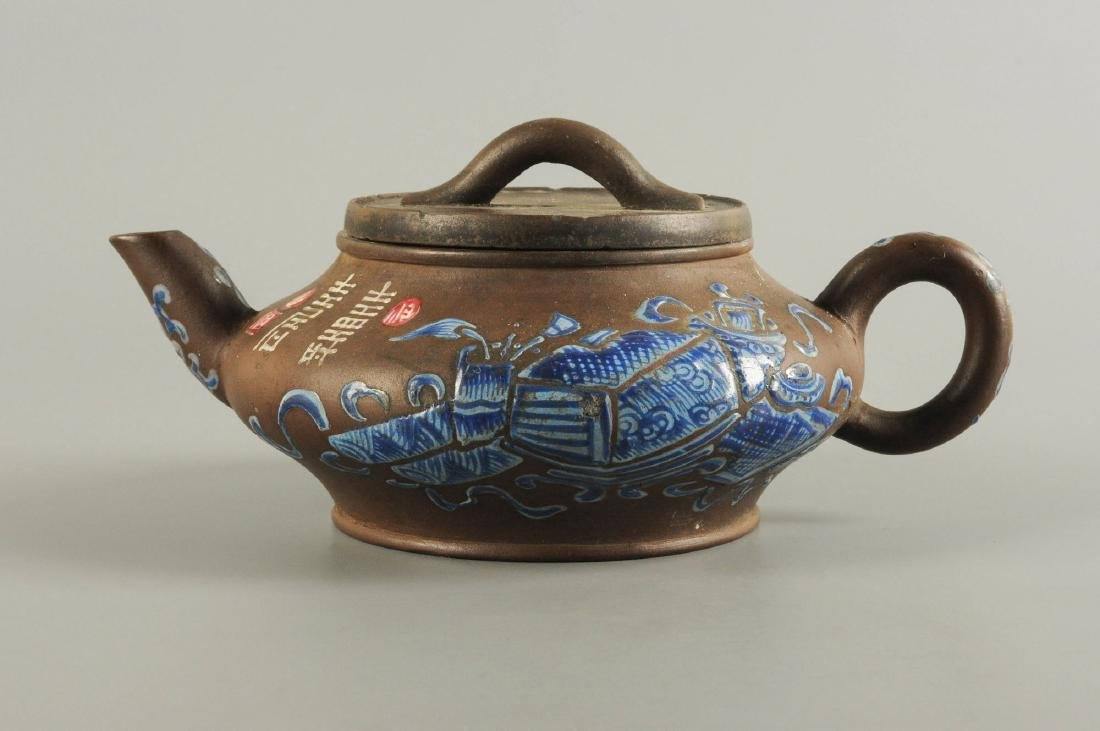 A Yixing teapot decorated with floral design. Unmarked.