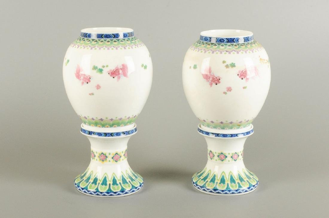 A pair of polychrome porcelain vases on a porcelain