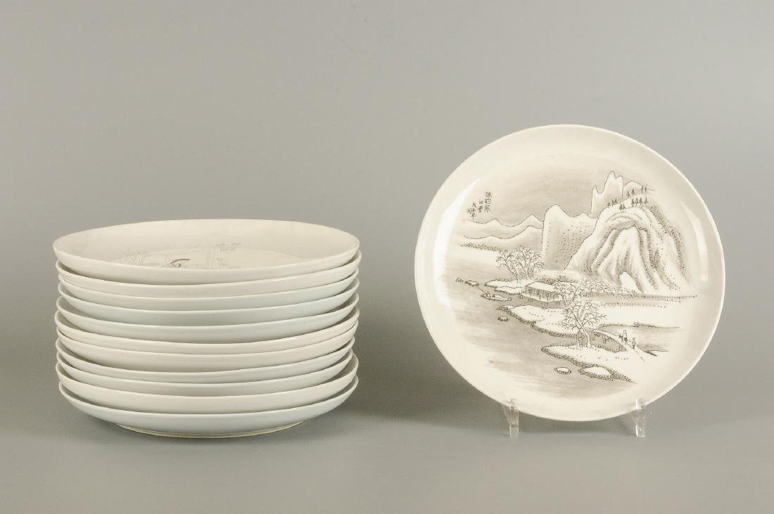 A set of 12 large plates with varying decoration, i.a.