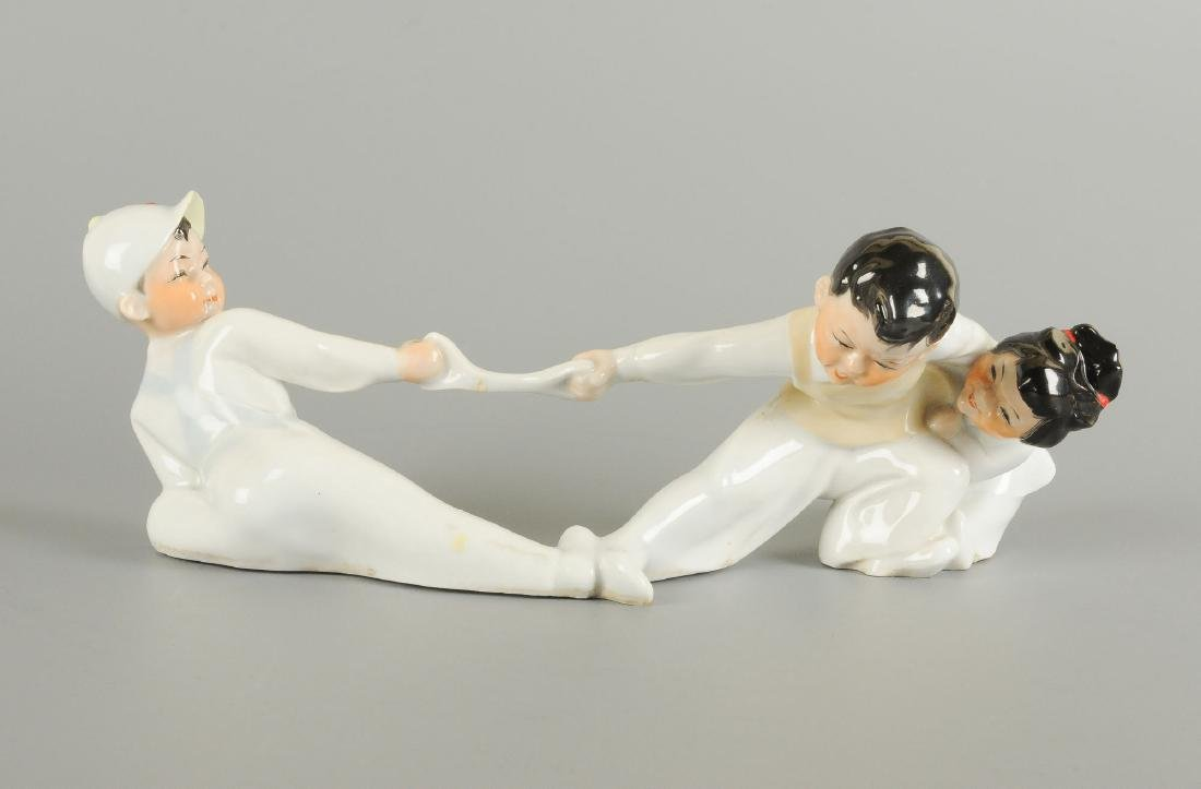 A polychrome porcelain statue of three children, two of
