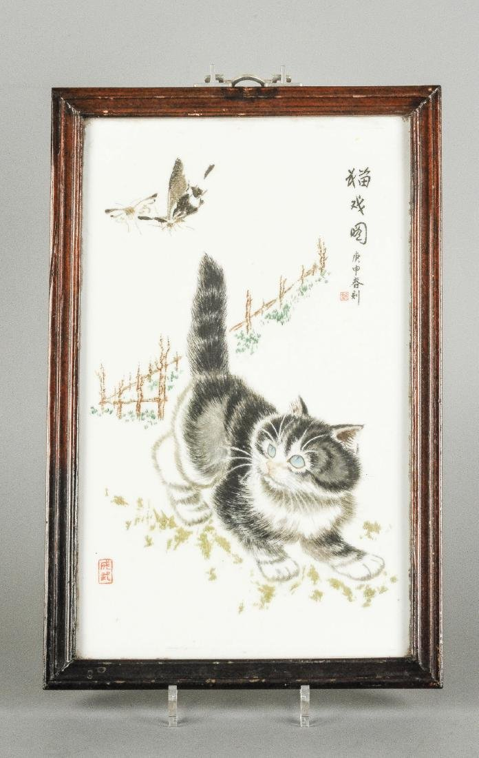 A polychrome porcelain plaque decorated with a cat,