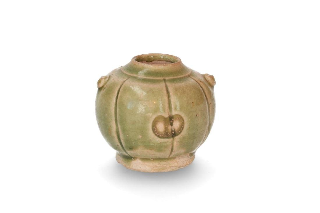 A celadon green pottery jar with a ribbed belly. China,