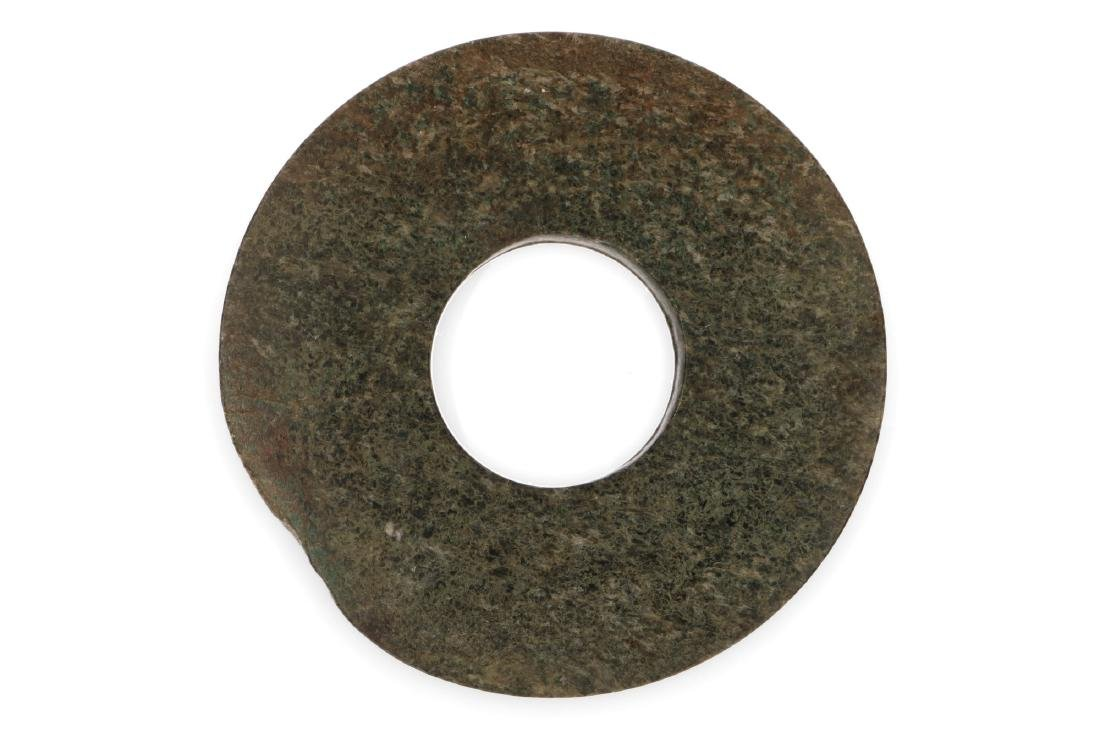 An archaïc large green jade bi-disc. The plain formed