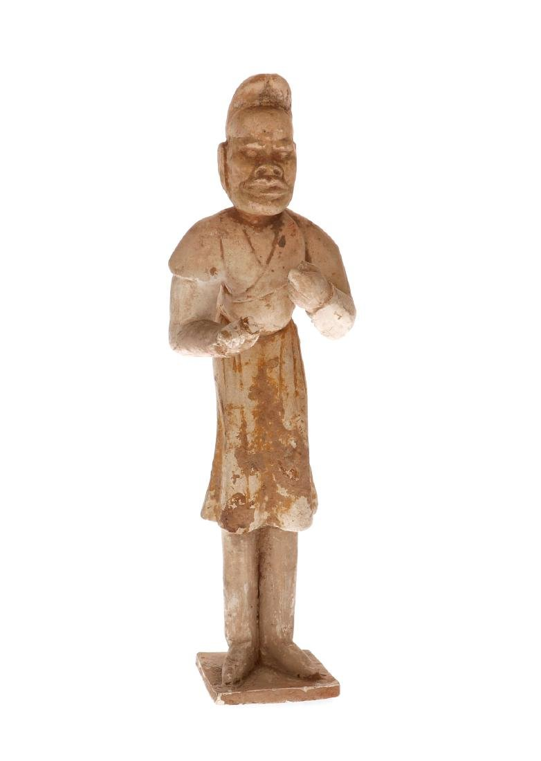 An earthenware unglazed sculpture of a male attendant,