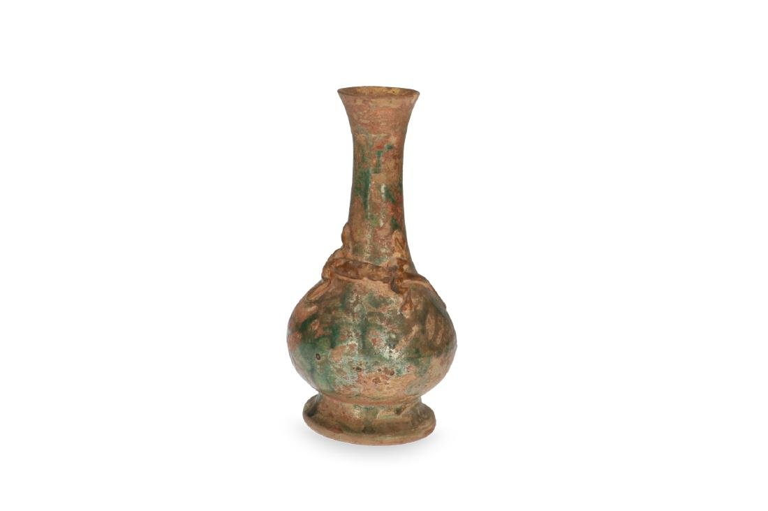 A pottery green glazed bottle vase with a lizzard