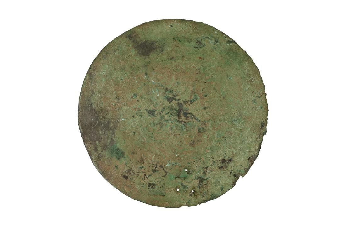 A bronze mirror with 'lion and grape' decor.