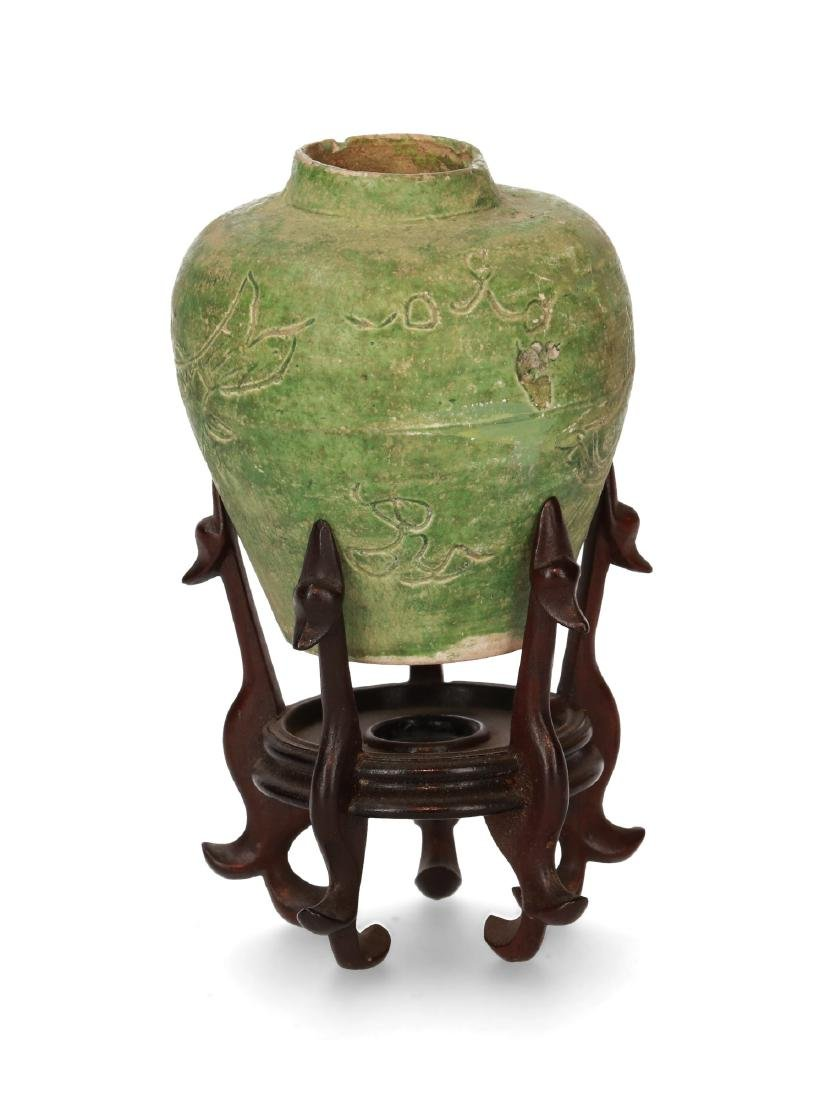 A green glazed pottery jar with a carved decor of fish.