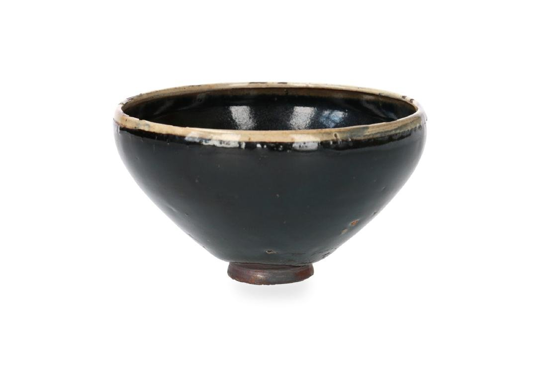 A black glazed bowl with cream glazed rim. China,