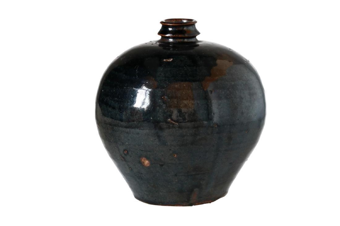 A round shaped black glazed jar with girded neck. The