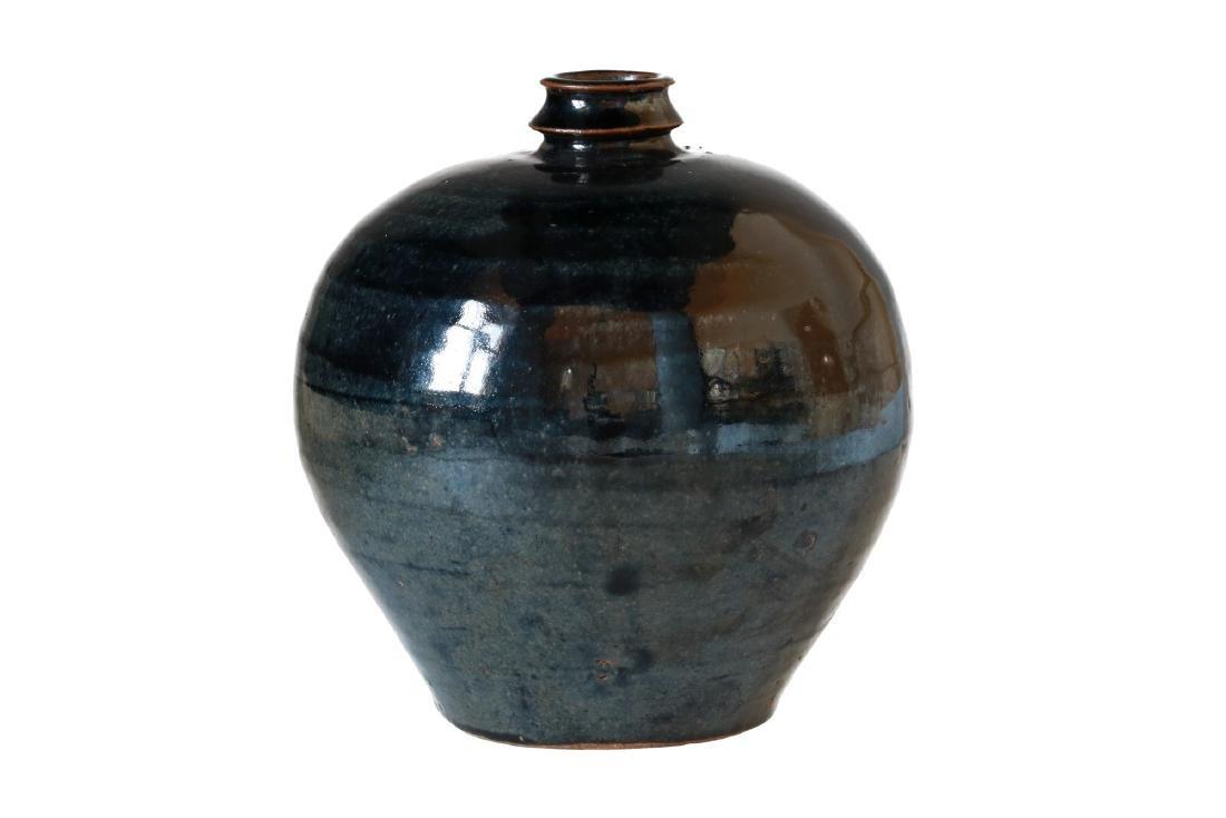 A round shaped black glazed jar with girded neck. The - 2