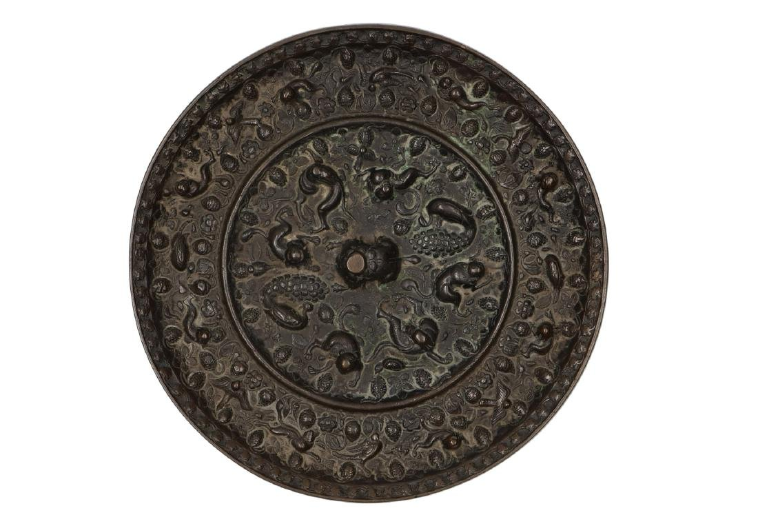 A bronze mirror with 'lion and grape' decor. Old