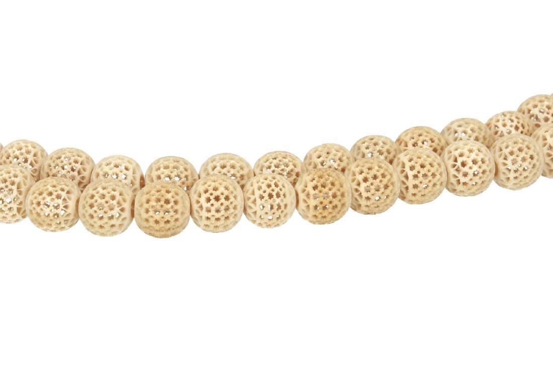 A long string of open work globular bone beads. China,