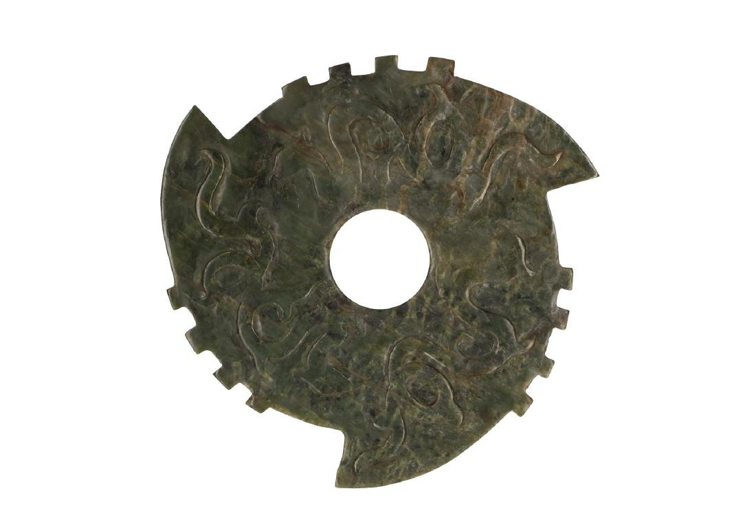 A nephrite jade bi disc with bold carving of dragons in