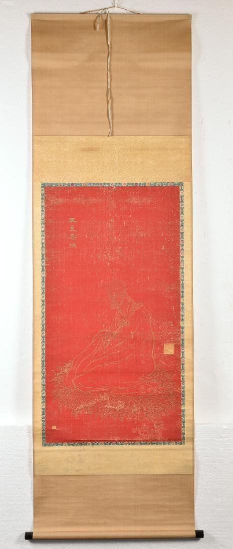 A red silk paper hanging scroll with sitting Lohan.