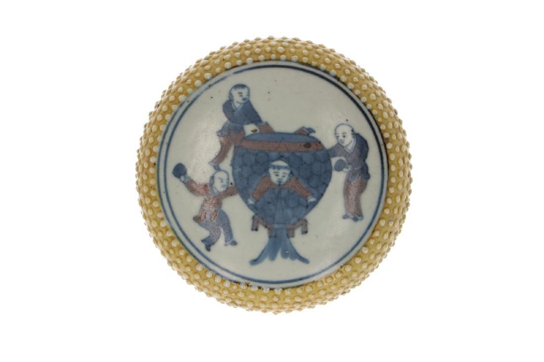 A polychrome porcelain lidded circular box with a